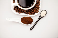 Composition with coffee cup, coffee powder, sugar and beans Royalty Free Stock Images