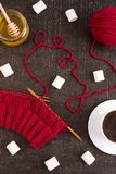 Composition with coffee, knitting and marsh-mallows. Composition with coffee, honey, red knitting and marsh-mallows on black grunge background Stock Images