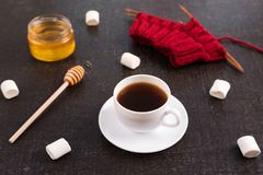 Composition with coffee, knitting and marsh-mallows. Composition with coffee, honey, red knitting and marsh-mallows on black grunge background Stock Image