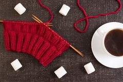 Composition with coffee, knitting and marsh-mallows. Composition with coffee, red knitting and marsh-mallows on black grunge background Stock Photography