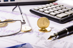 Composition of the coins, calculator and charts Stock Photography