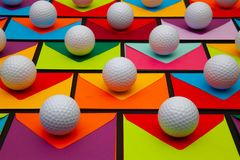Composition with colored envelopes and golf balls on the table