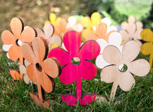 Composition of colored wooden flowers in the grass. Stock Photography