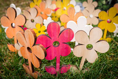 Composition of colored wooden flowers in the grass. Stock Image