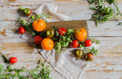 Composition of colorful ripe summer tomatoes. Flatlay. White vintage wooden background Royalty Free Stock Photos