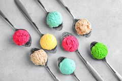 Composition with colorful scoops of ice-cream in spoons. On light background royalty free stock photos