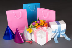 Composition of colorful tulips, gift boxes and birtday hats Royalty Free Stock Photo