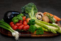 Composition with colorful vegetables. Wooden plate with fresh  colorful  various vegetables on a dark background Stock Photo