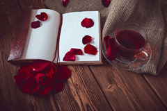 Composition consist of roses, hibiscus tea cup and note book on a wooden surface Stock Photography