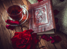 Composition consist of roses, hibiscus tea cup and note book on a wooden surface Stock Photo