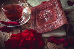 Composition consist of roses, hibiscus tea cup and note book on a wooden surface Royalty Free Stock Images