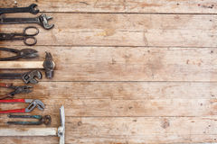 Composition of construction tools on an old battered wooden surface of tools: pliers, pipe wrench, screwdriver, hammer, metal shea Royalty Free Stock Images
