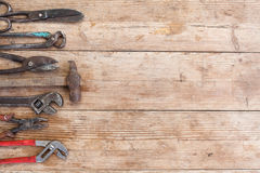 Composition of construction tools on an old battered wooden surface of tools: pliers, pipe wrench, screwdriver, hammer, metal shea Royalty Free Stock Image