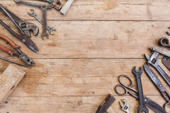 Composition of construction tools on an old battered wooden surface of tools: pliers, pipe wrench, screwdriver, hammer, metal shea Stock Images