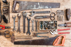 Composition of construction tools on an old battered wooden surface of tools: pliers, pipe wrench, screwdriver, hammer, metal shea Stock Photo