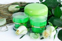 Composition cosmétique de 3 bouteilles crèmes avec des roses Photographie stock