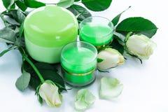 Composition cosmétique de 3 bouteilles et roses crèmes Image stock
