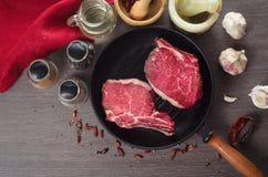 Composition crue en bifteck d'oeil de nervure de viande fraîche dans la casserole de gril sur le fond en bois Photo stock