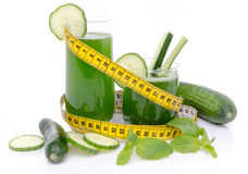 Composition with cucumber juice, fresh cucumbers and a tape meas Royalty Free Stock Photo