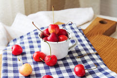Composition of cup and berries. Cherries is the reason of the longevity . White retro cup and berries on a checkered napkin on the table. Retro cup and berries Stock Images