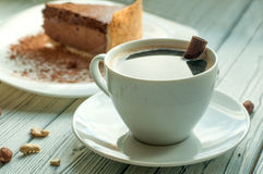 A composition with a cup of black coffee and a peace of a chocolate cheese cake decorated with cocoa powder and nuts Royalty Free Stock Photography