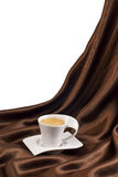 Composition with cup of coffee over brown satin. Stock Photo