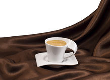 Composition with cup of coffee over brown satin. Royalty Free Stock Image