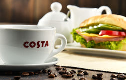 Composition with cup of Costa Coffee coffee and sandwich Royalty Free Stock Photo