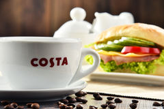 Composition with cup of Costa Coffee coffee and sandwich Royalty Free Stock Photos