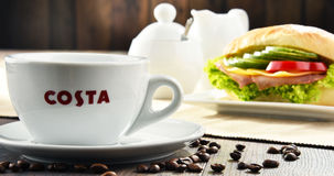 Composition with cup of Costa Coffee coffee and sandwich Stock Images