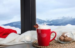 Composition with cup of hot winter drink on windowsill. Space for text royalty free stock photos