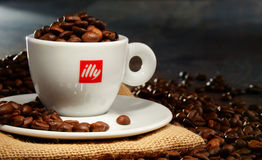 Composition with cup of Illy coffee and beans Royalty Free Stock Photos