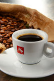 Composition with cup of Illy coffee and beans Royalty Free Stock Photo