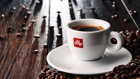 Composition with cup of Illy coffee and beans Royalty Free Stock Images