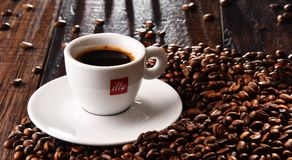 Composition with cup of Illy coffee and beans Stock Image