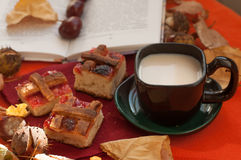 A A composition with a cup of milk coffee, several pieces of homemade pie, an opened book, chestnuts and dry autumn leaves on a re Stock Images