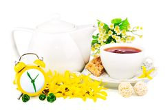 Composition from cup of tea, clock and spring flowers. Composition from cup of tea, yellow clock and spring flowers isolated on white background Royalty Free Stock Images