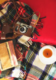 Composition with  cup of tea, vintage camera, old books on sofa with plaid. Top view. Stock Photography
