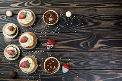 Composition of cupcakes, cookies and candies on dark wooden background. Valentine concept. Composition of cup cakes, cookies and candies on dark wooden Stock Images