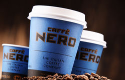 Composition with cups of Caffe Nero coffee and beans Royalty Free Stock Image