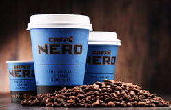Composition with cups of Caffe Nero coffee and beans Royalty Free Stock Images