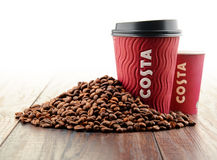 Composition with cups of Costa Coffee coffee and beans Stock Images