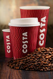 Composition with cups of Costa Coffee coffee and beans Stock Photography