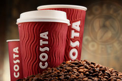 Composition with cups of Costa Coffee coffee and beans Royalty Free Stock Photo
