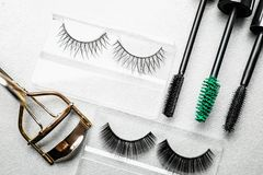 Composition with curler and false eyelashes. On light background Royalty Free Stock Photo