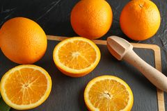 Composition with cutting board, oranges and wooden juicer. Closeup stock image
