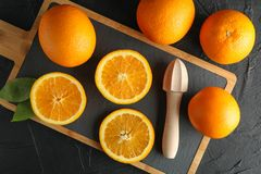 Composition with cutting board, oranges and wooden juicer. Top view stock photography