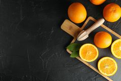 Composition with cutting board, oranges and wooden juicer. Top view, space for text stock photos