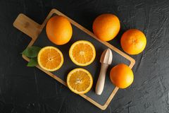 Composition with cutting board, oranges and wooden juicer. Top view. Space for text royalty free stock image