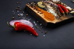 Composition with a cutting board, spices and hot pepper on a wooden background Royalty Free Stock Image